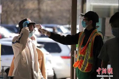 加拿大多伦多一家华人超市的工作人员在入口处对顾客逐一测量体温。(<a target='_blank' href='http://www.chinanews.com/'>中新社</a>记者余瑞冬摄)