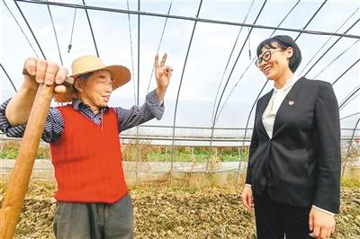留澳海归岳文雯(右)与农户亲切交谈。